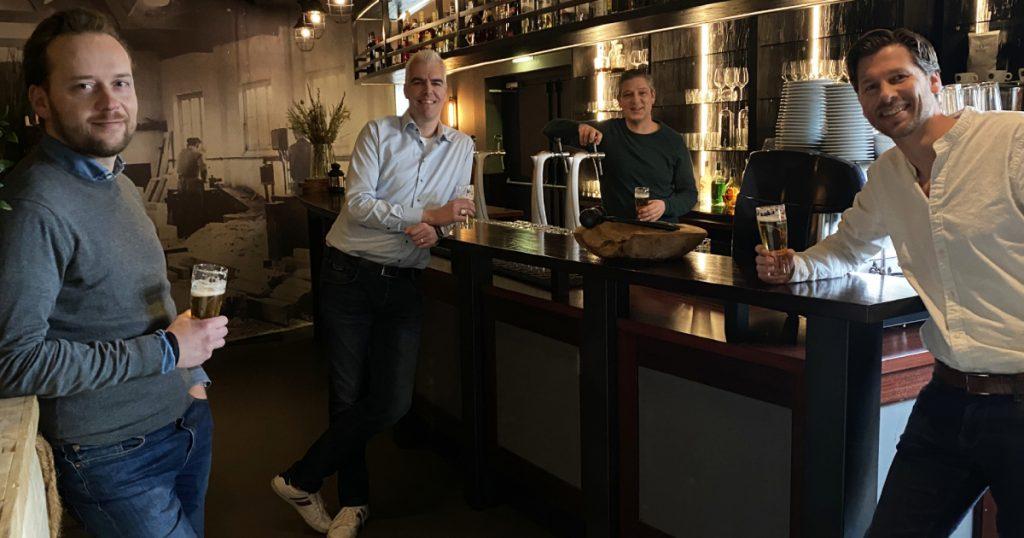 Willem van Tilburg (links), Twan van Zandvoort (midden) en Mark van de Bogaert (rechts) op bezoek bij De Werkplaets van Bart van Gaal (achter de bar).